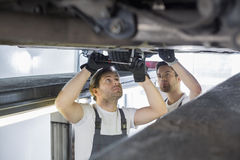 Maintenance engineers repairing car in workshop Royalty Free Stock Photography