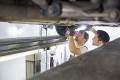 Maintenance engineers repairing car in workshop Stock Photography