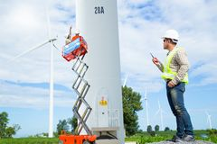 Maintenance engineers working at wind turbine power generator. Station with mobile crane Royalty Free Stock Image
