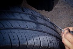 Maintenance fixing flat tire problem from nail sharp screw. car. Maintenance fixing flat tire problem from nail sharp screw. hole on car tyre stock images