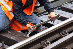 Maintenance of railroad. Worker tightens the screw on railroad with two spanners in hands Stock Photo