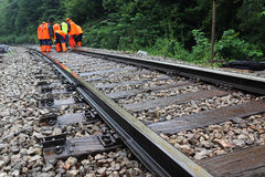 Maintenance of railroad. Workers in orange  raincoats repair railroad on rainy day Stock Image