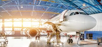 Maintenance and repair of aircraft in the aviation hangar of the airport, view of a wide panorama.  stock image