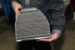 Maintenance and repair of the car. Old cabin filter. Royalty Free Stock Images
