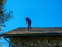 Maintenance of the roof of an old village house with slate tiles. royalty free stock photos