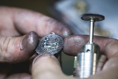 Maintenance of silver pendant in jewellery workshop Royalty Free Stock Image
