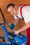 Maintenance of a small tiller machine Stock Photography