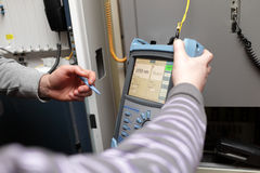 Maintenance technicians with reflectometer. A maintenance technicians with reflectometer at a telecom site Royalty Free Stock Images