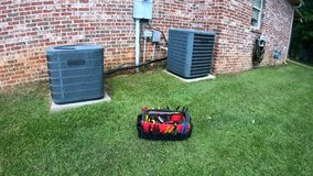 Maintenance tool bag in front of home HVAC Air Conditioner units