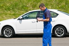 Maintenance worker in blue suit, records car data royalty free stock image