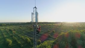 Maintenance worker carry out repairs high up on communications tower using safety equipment on background of sunset. Maintenance worker carry out repairs high up stock video footage