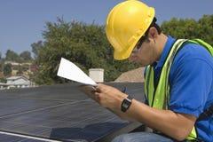 Maintenance Worker Making Notes Near Solar Panels. Side view of young maintenance worker making notes near solar panels on rooftop Stock Images