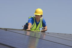 Maintenance Worker Measuring Solar Panels Royalty Free Stock Photo