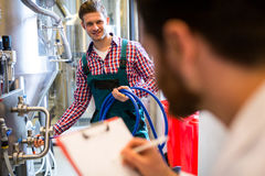 Maintenance workers examining brewery machine Royalty Free Stock Photos