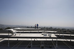 Maintenance Workers Near Solar Panels On Rooftop stock image
