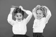 Maintenez les cheveux tressés pour le regard rangé Les élèves d'enfants jouent avec de longs cheveux tressés Salon de coiffeur Co photographie stock