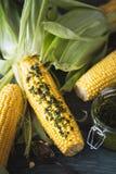 Mais auf dem Pfeiler bereit, auf Grill mit Chimichurri-Soße gegrillt zu werden stockfotografie