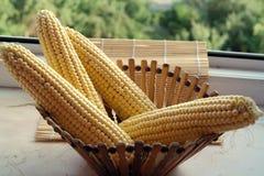 Mais im hölzernen Korb auf einem Fenster, das den Garten im Dorf übersieht Stockfotografie