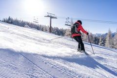 Mais skiier fêmea vestido no revestimento vermelho aprecia inclinações fotografia de stock royalty free