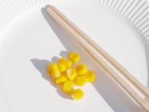 Mais und Ess-Stäbchen Stockfotos