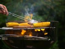 Mais und Würste auf einem lodernden Grill Lizenzfreie Stockfotografie