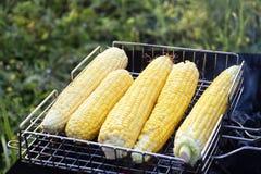 Mais wird auf dem Grill mit Kohlen draußen gebraten Stockfoto