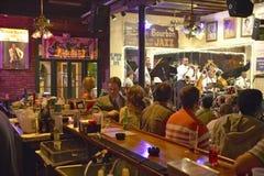 Maison保守主义者与Dixieland带的爵士乐俱乐部和执行在酒吧后的晚上的喇叭演奏员与饮用的顾客在法国Q 免版税库存照片
