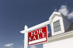 Maison à vendre le signe d'immobiliers devant la maison Image stock