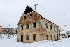 Maison abandonnée avec les fenêtres cassées et les briques tombées couvertes dans la neige Images stock