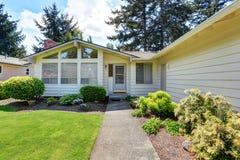Maison américaine avec l'équilibre de voie de garage et la pelouse soignée autour Image stock