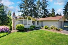 Maison américaine avec l'équilibre de voie de garage et la pelouse soignée autour Photo libre de droits