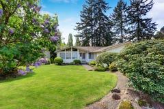 Maison américaine avec l'équilibre de voie de garage et la pelouse soignée autour Photographie stock libre de droits