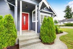 Maison américaine classique avec l'équilibre de voie de garage et la porte d'entrée rouge Photographie stock
