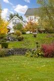 Maison américaine de ferme de cheval blanc pendant la chute avec l'herbe verte. Photographie stock