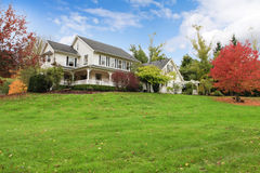 Maison américaine de ferme de cheval blanc pendant la chute avec l'herbe verte. Image stock