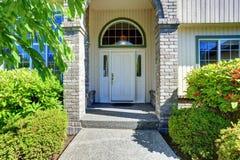 Maison américaine extérieure avec le porche concret de plancher avec des colonnes Photographie stock libre de droits