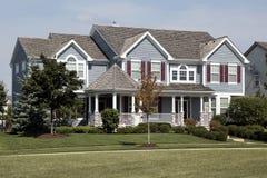 Maison avec les obturateurs et le toit rouges de cèdre photos libres de droits