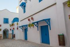 Maison blanche avec les fenêtres et les portes et les fleurs bleues, Yasmine Hammamet, Tunisie photographie stock libre de droits