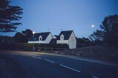 Maison blanche la nuit avec la lumière de lune au ciel nocturne bleu-foncé images stock