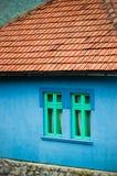 Maison bleue de côté de pays avec les fenêtres vertes Photos stock