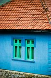 Maison bleue de côté de pays avec les fenêtres vertes Images libres de droits