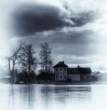 Maison bleue vibrante de sépia de vintage vertical sur le fond des eaux Photo libre de droits