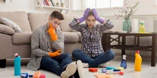 Maison choquée de nettoyage de couples avec un bon nombre d'outils Photo libre de droits