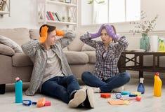 Maison choquée de nettoyage de couples avec un bon nombre d'outils Image stock
