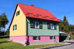 Maison colorée de famille avec le toit en métal et les abat-jour de fenêtre en bois décorés entourés avec les elfes de jardin et  image libre de droits