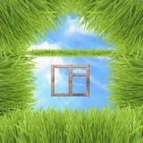 Maison conceptuelle d'herbe verte sur le fond de ciel Photographie stock