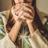 Maison confortable Femme avec la tasse de la boisson chaude par la fenêtre Regarder le thé de fenêtre et de boissons bonjour avec images libres de droits