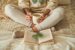 Maison confortable La belle fille lit un livre sur le lit bonjour avec le thé Détente de fille assez jeune Le concept de la lectu photos stock
