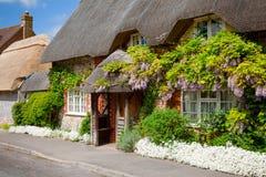 Maison couverte de chaume anglaise traditionnelle avec la décoration de fleur dans Sou photos libres de droits