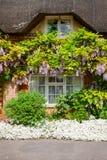 Maison couverte de chaume anglaise traditionnelle avec la décoration de fleur dans Sou photos stock